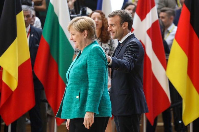 Angela Merkel and Emmanuel Macron in front of various European flags.