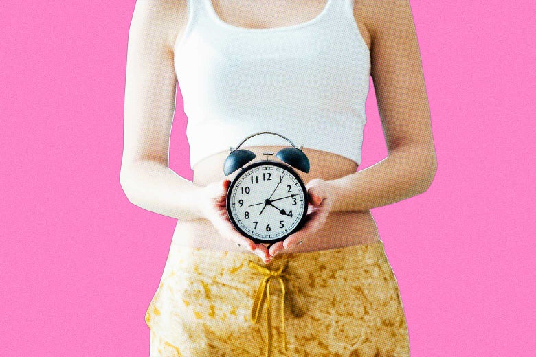 A woman holding an analog clock in front of her lower abdomen.