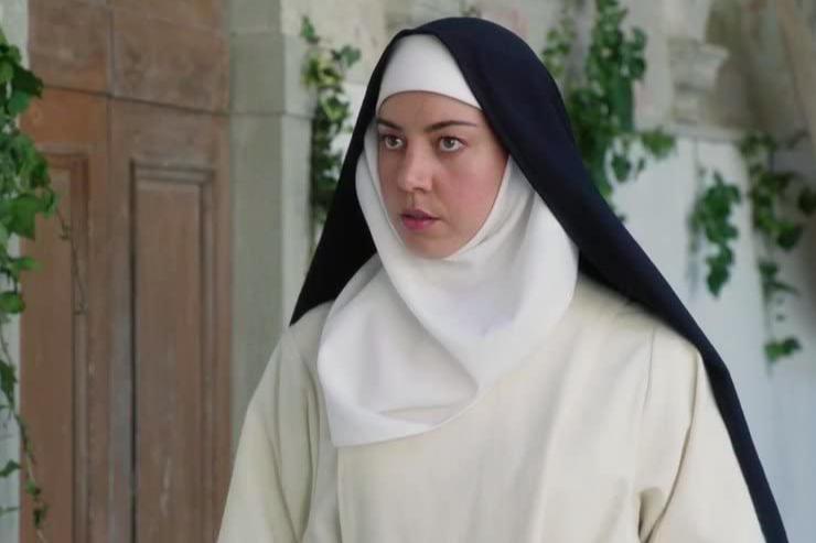 Aubrey Plaza wears a white nun's habit with a black hood.
