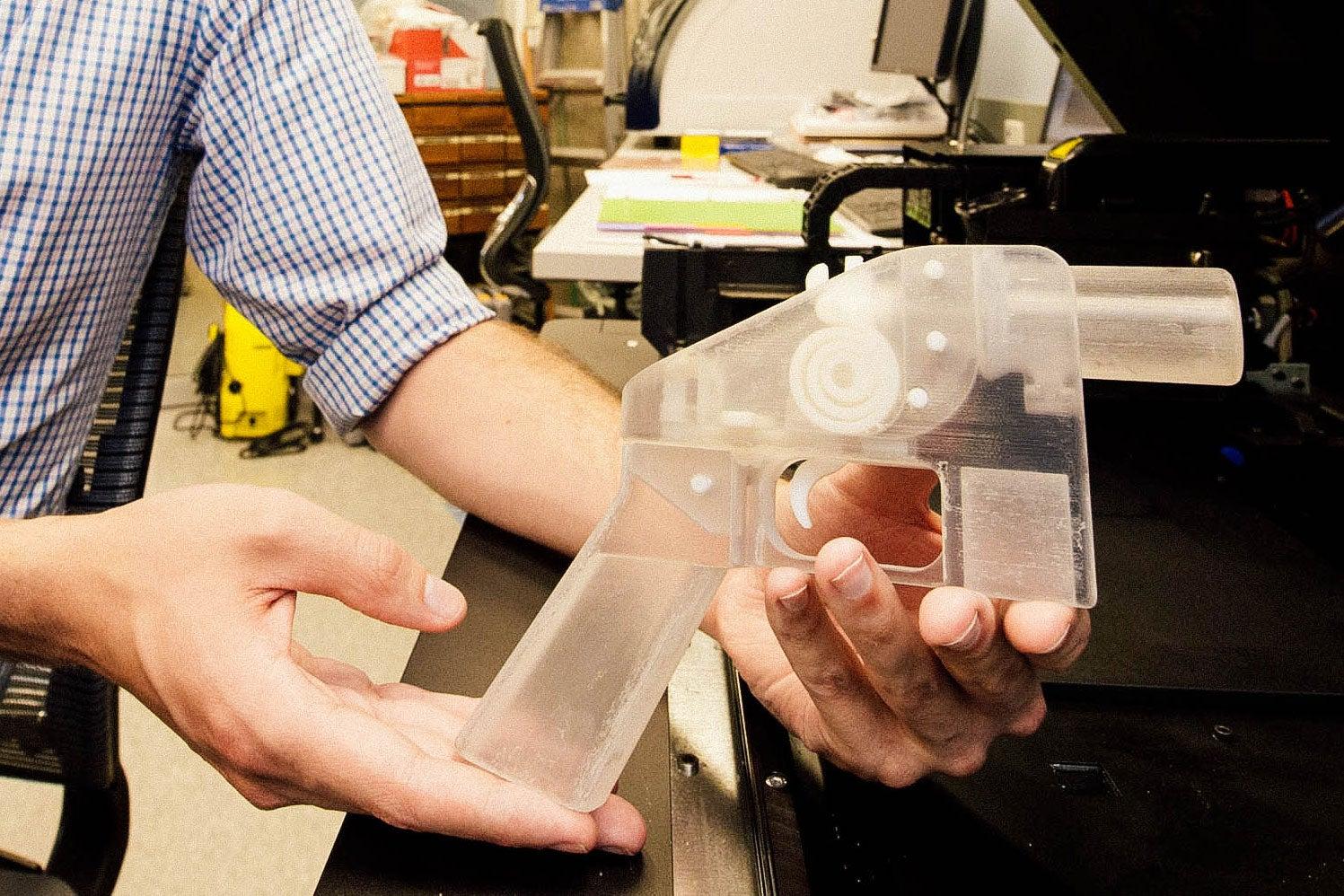 Daniel Southwick shows off a gun made by a 3D printer.