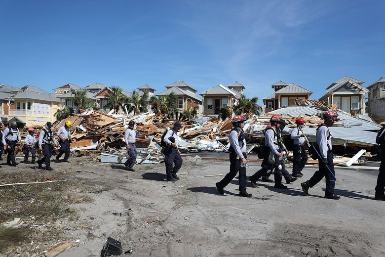 A line of rescue workers passes a row of collapsed houses. Behind them, there are palm trees, and the sky is blue.