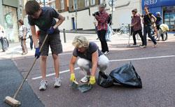 Members of the public sweep the streets in Clapham Junction, in south London, on August 9, 2011, of debris following a third night of unrest in London. Click image to expand.
