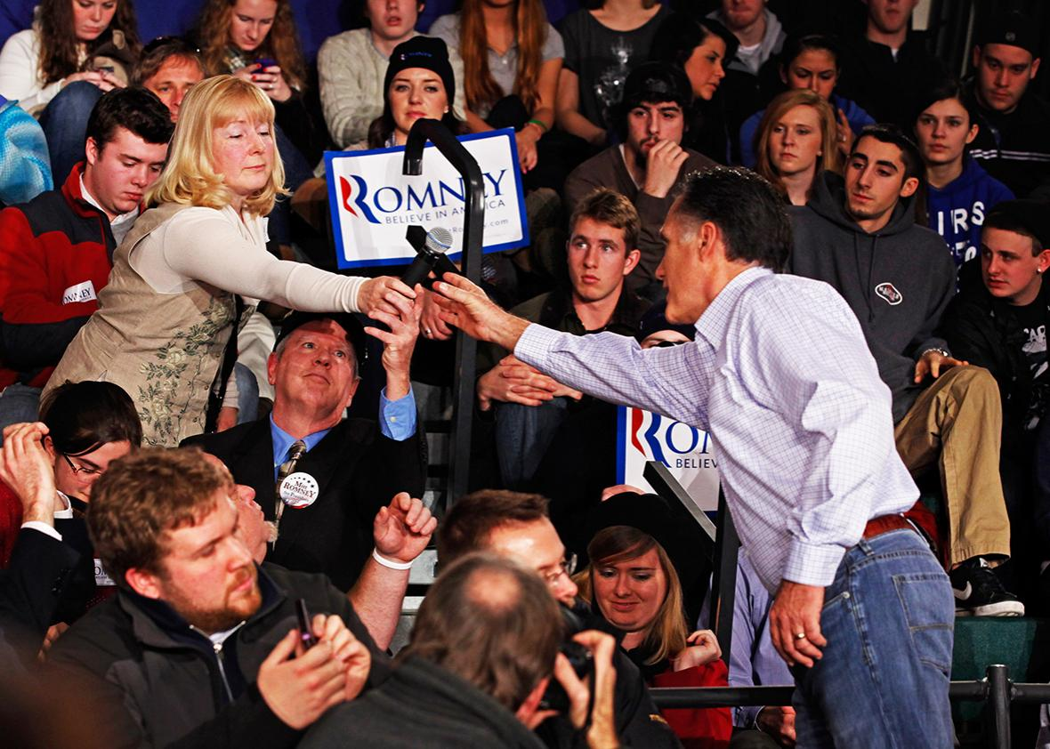 Republican presidential candidate, former Massachusetts Gov. Mitt Romney takes back a microphone from a woman who asked a question during a campaign town hall meeting at Central High School January 4, 2012 in Manchester, New Hampshire.