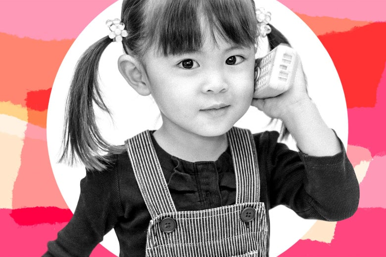 Smiling toddler girl in pigtails holding a phone up to her ear