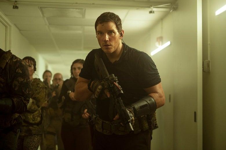 chris pratt, holding a gun, leads a group of people