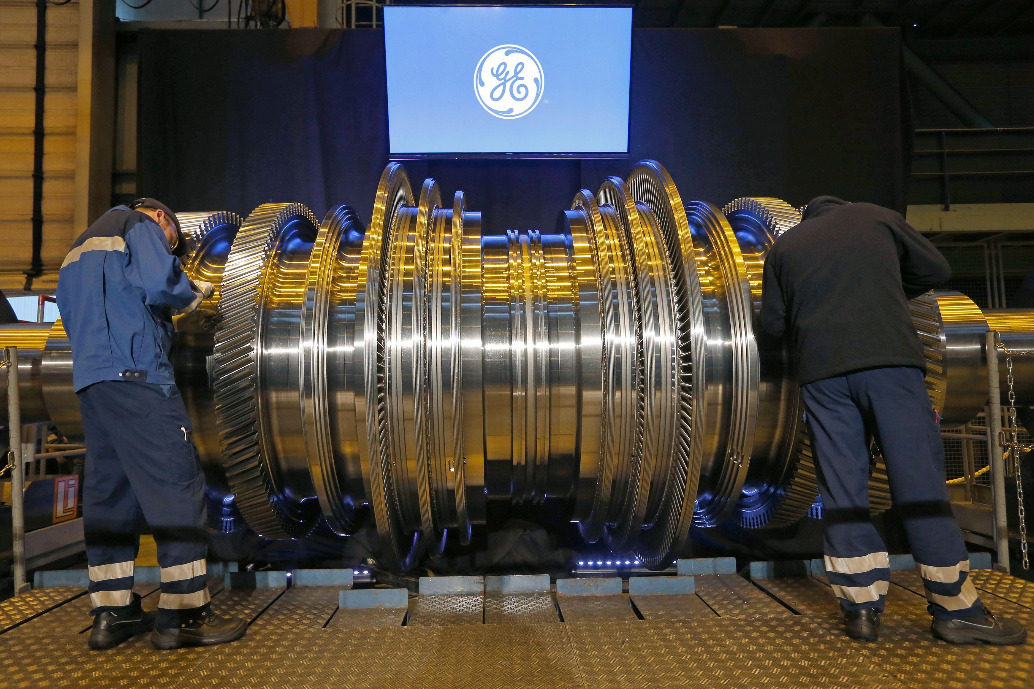 Employees work on a General Electric turbine.