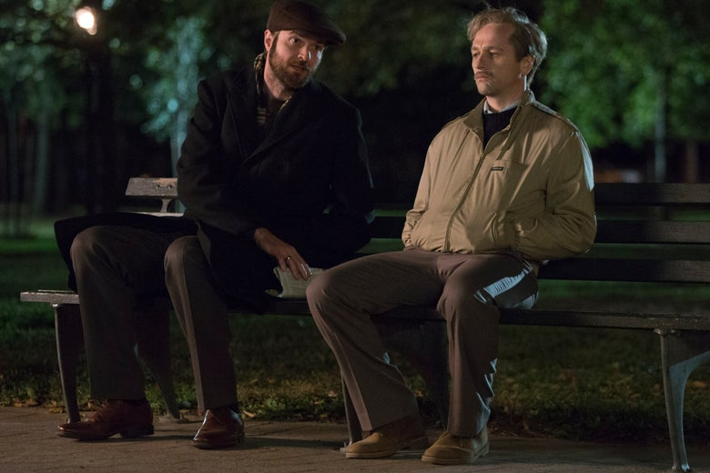 Philip (Matthew Rhys) and Oleg (Costa Ronin) have a conversation on a park bench in FX's The Americans. They are both young men. Oleg, to the left, has a short beard and wears dark clothes and a flat cap. Oleg, to the right, wears a khaki jacket, pants, and shoes.