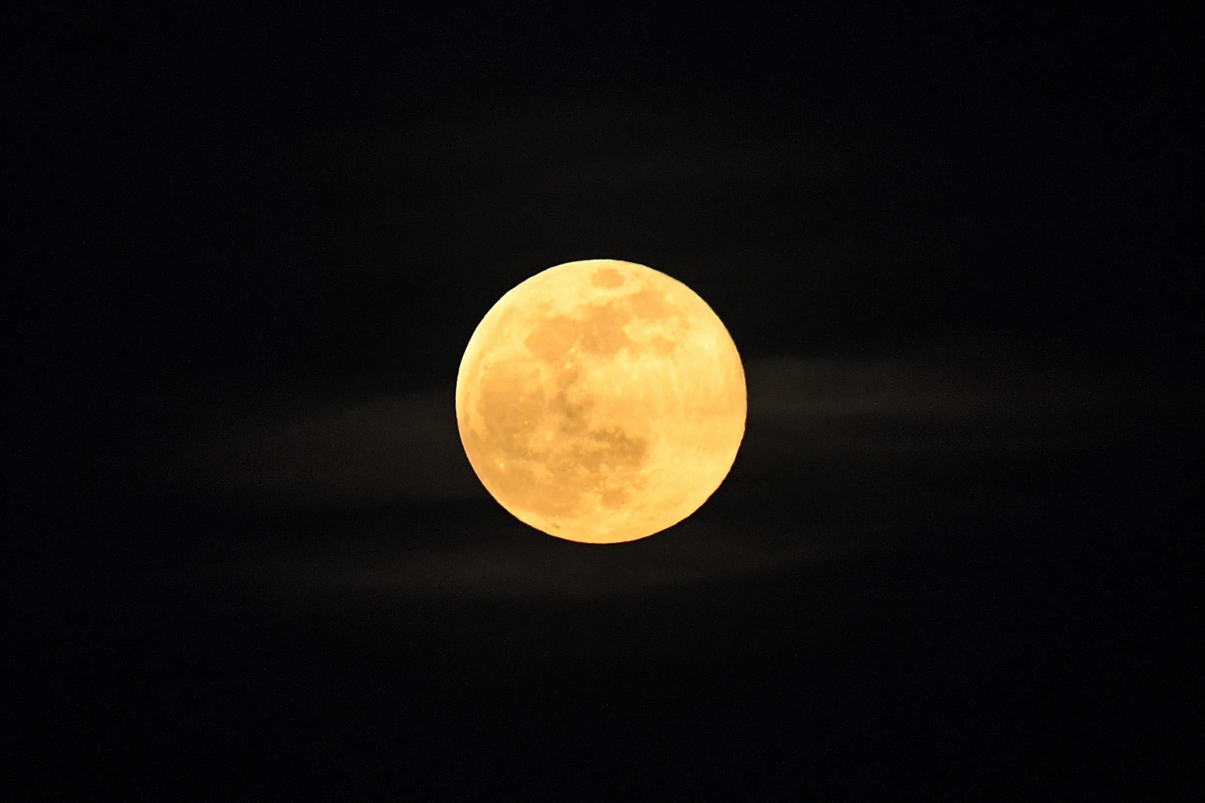 Yellow moon in the night sky.