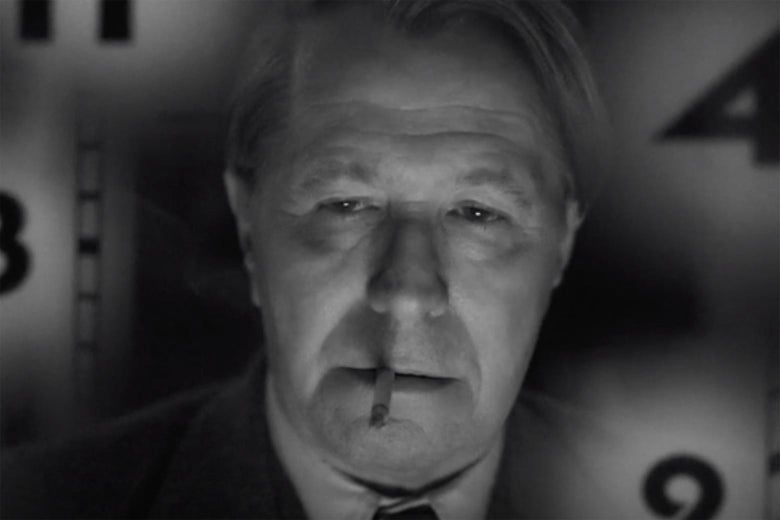 Black-and-white still of Gary Oldman with a cigarette in his mouth and numbers behind him.