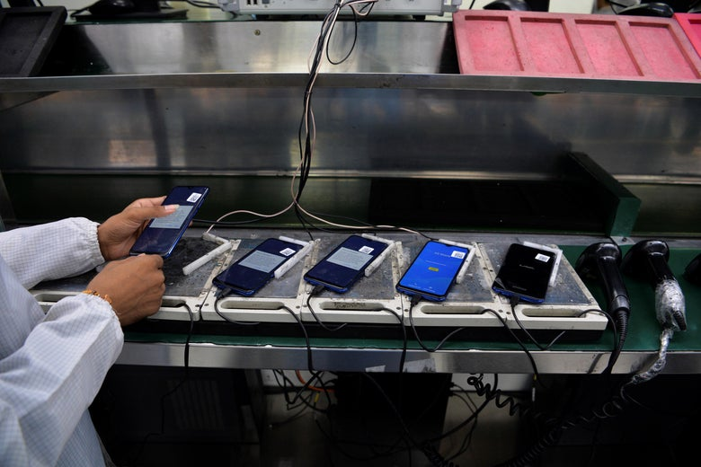 A worker assembles mobile phones at an Indian Lava phone manufacturer factory in Noida on August 22, 2019.