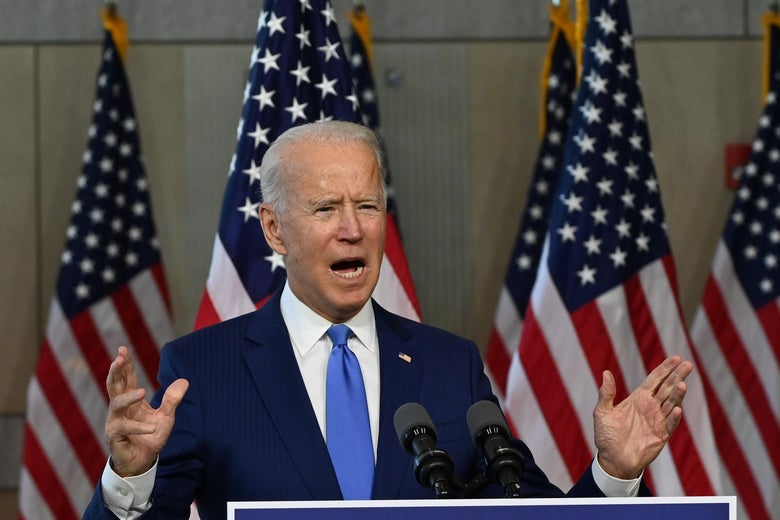 Biden gestures with his hands while speaking at a podium