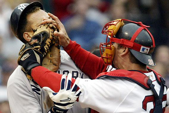 New York Yankees' Alex Rodriguez (L) takes a punch from Boston Red Sox catcher Jason Varitek in the third inning at Fenway Park in Boston, Massachusetts July 24, 2004.