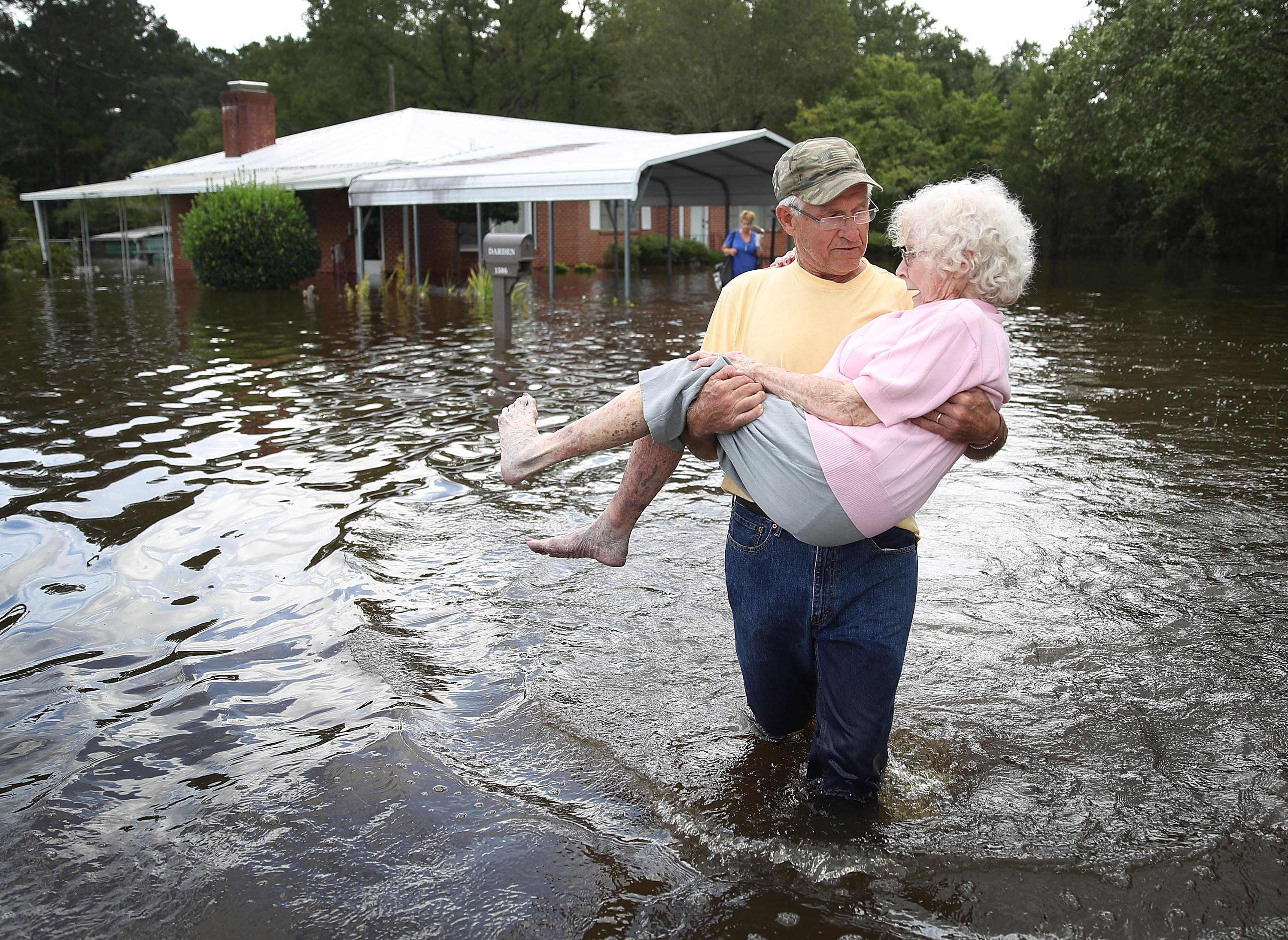 A man carries an older woman in knee-height water with a flooded house in the background.