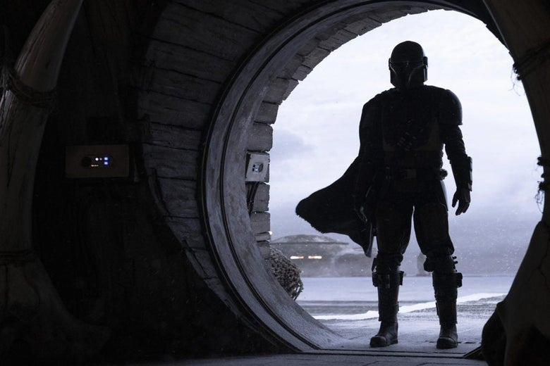A silhouette of a person wearing armor, a helmet, and a cape standing in a round doorway.