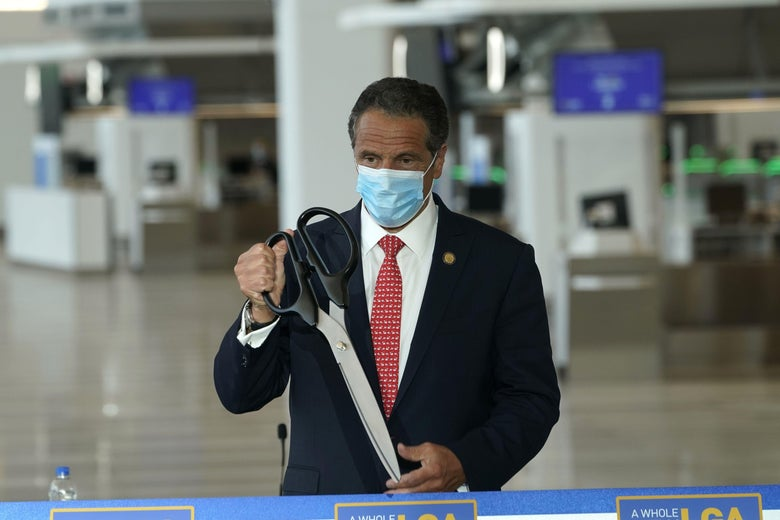 Cuomo wearing a surgical mask and holding a giant pair of scissors as he stands next to a ribbon in the terminal.