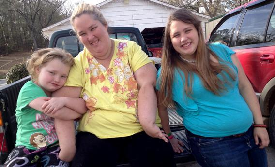 Honey Boo Boo (Alana Thompson), Mama (June Shannon), and Chubbs (Jessica Shannon) sitting on a pickup truck bed in the Season 2 Premiere of Here Comes Honey Boo Boo.