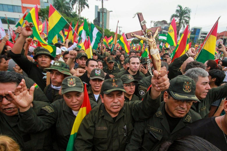A police officer holds a crucifix among comrades and people taking to the streets of Santa Cruz to celebrate the resignation of Bolivian President Evo Morales on November 10, 2019.