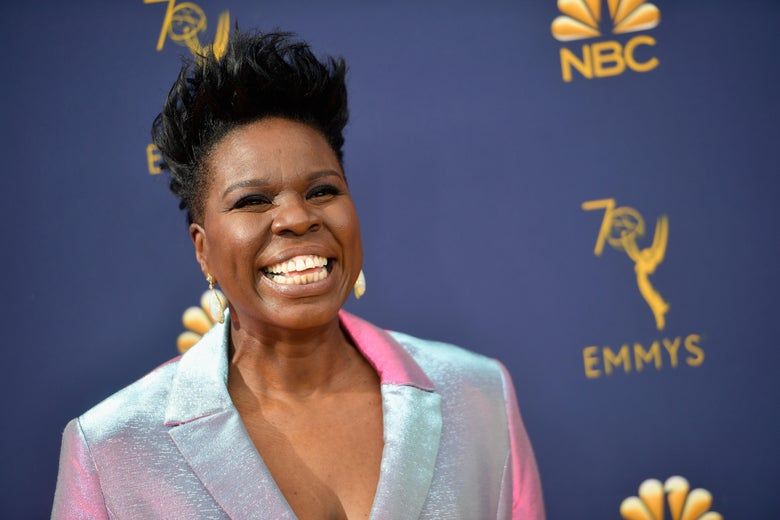 Leslie Jones smiles on the Emmy's red carpet, wearing an iridescent silver suit.