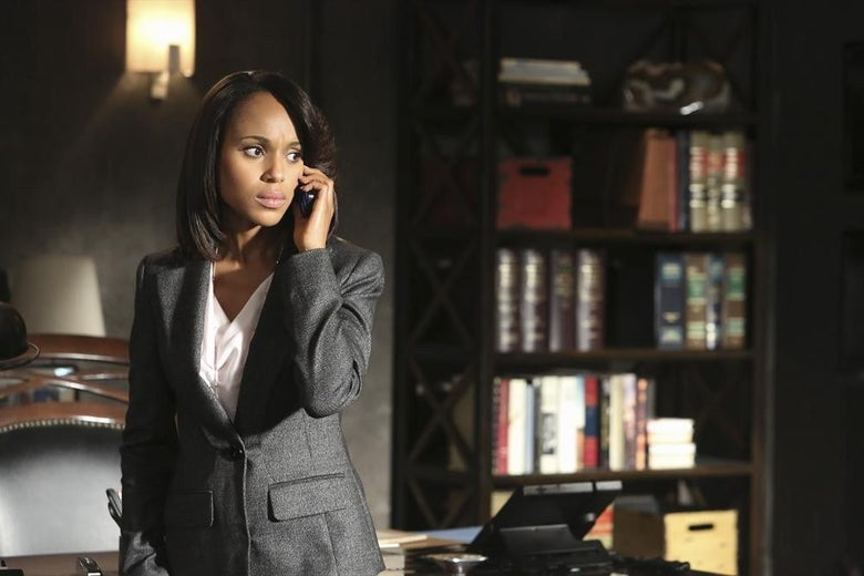 In an office, Kerry Washington holds a phone to her ear.