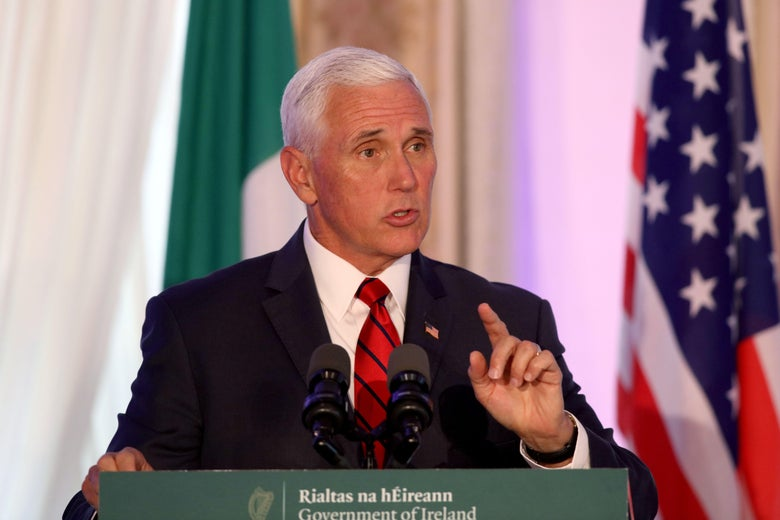 Vice President Mike Pence speaks while standing in front of Irish and American flags.