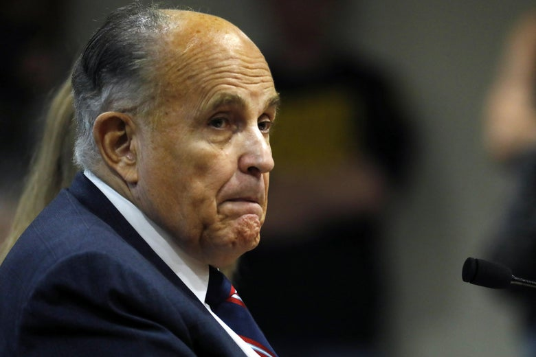 Rudy Giuliani looks sheepish, sitting in front of a mic