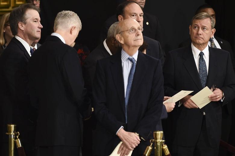 Brett Kavanaugh, Neil Gorsuch, Stephen Breyer, and John Roberts mill around at an event.