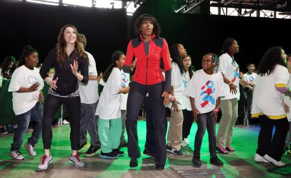 "First lady Michelle Obama dances with school children at a ""Let's Move!"" event."