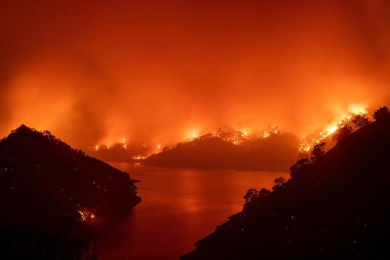 Flames surround Lake Berryessa during a wildfire.