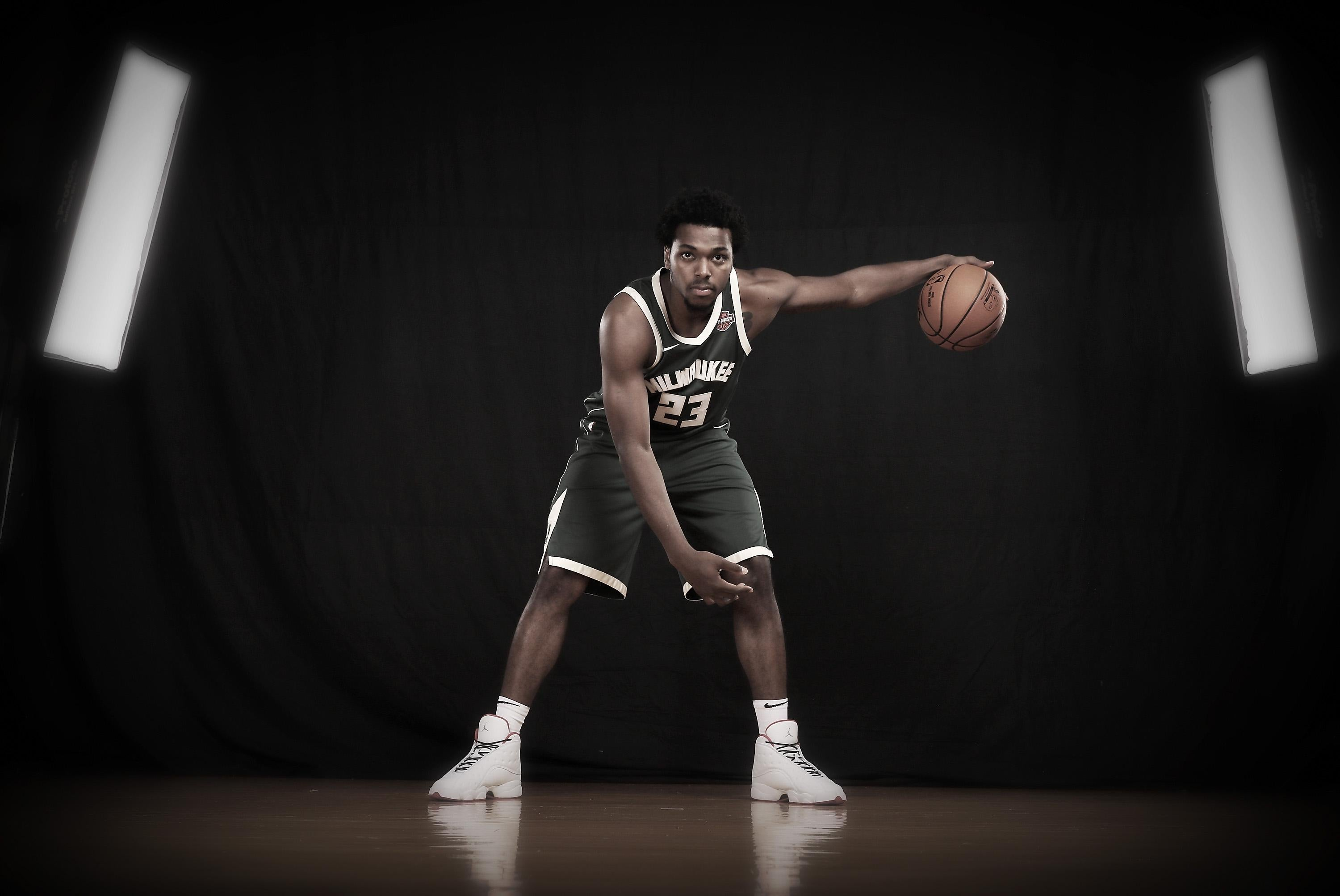 Milwaukee Bucks guard Sterling Brown dribbles a basketball against a black backdrop as part of a portrait during a photo shoot.