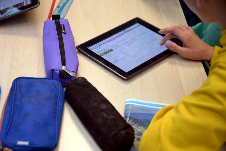 A child uses their tablet on a desk during class. There are three pencils pencil cases on the table next to the tablet.
