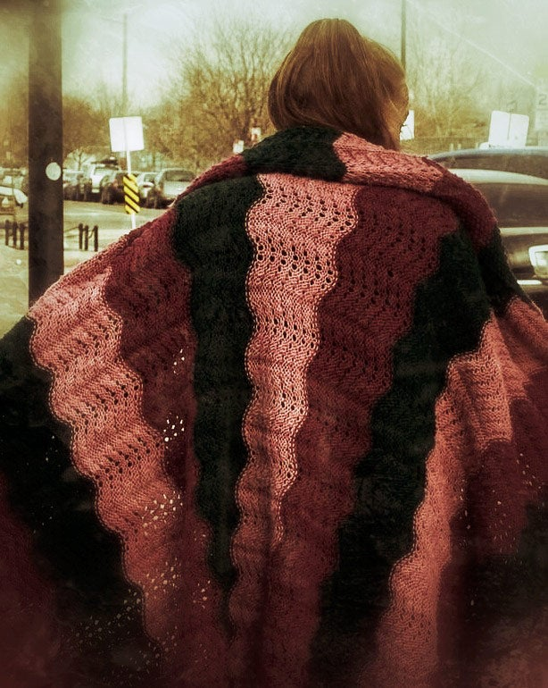 A woman wears a light blanket outside on a street. This image appears in the book EXPOSURE: Homelessness through the lens of art & poetry.