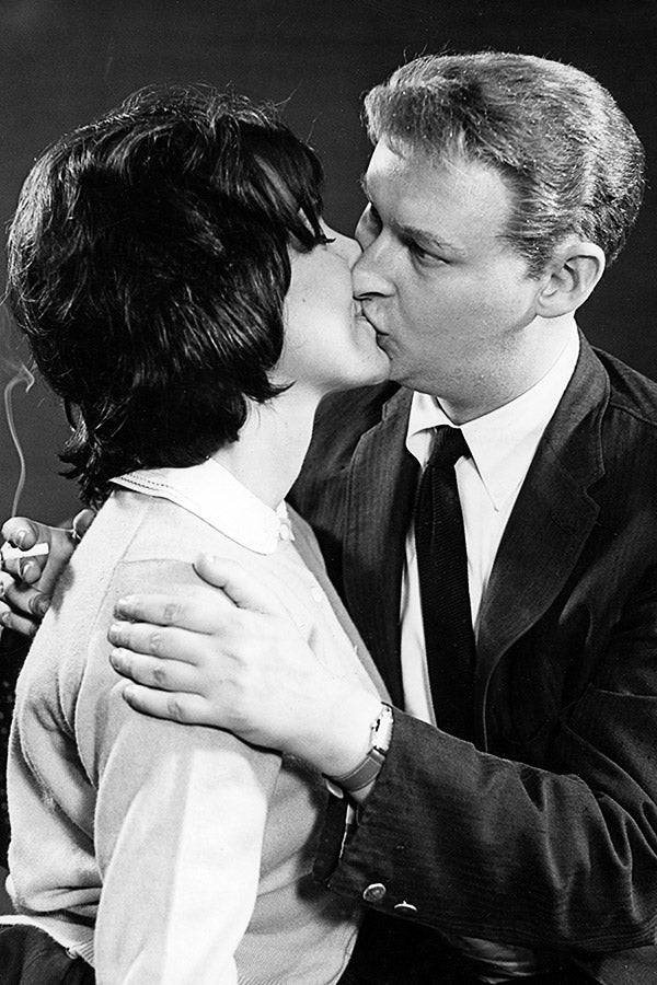 Mike Nichols planting a big kiss on Elaine May while holding a cigarette in his right hand.