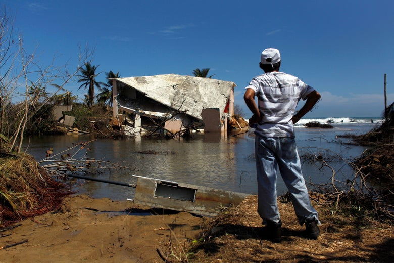 A man with his hands on his hips stands looking at a damaged house surrounded by water.