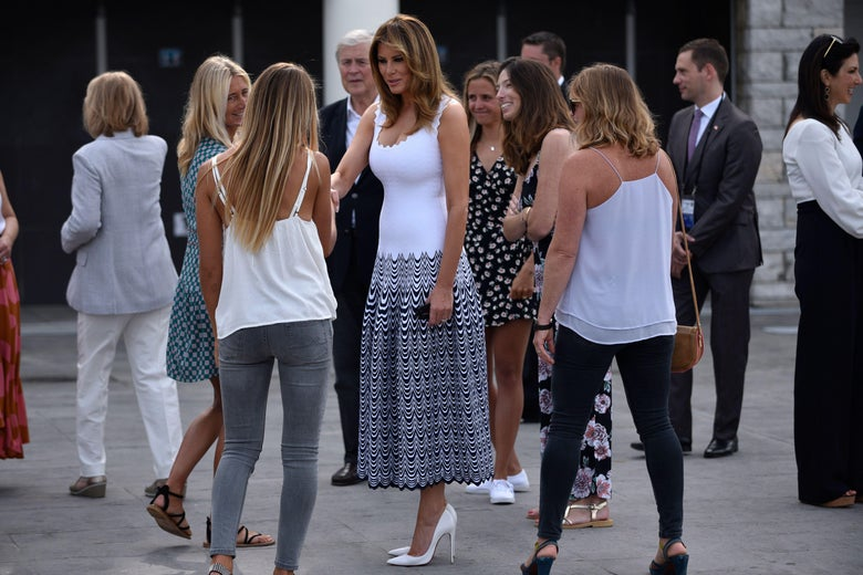 Melania Trump stands outside, surrounded by and talking to a group of young women. She wears white stilettos and a tight, white, low-cut sleeveless dress. The bottom half of the dress is covered in black wavy lines.