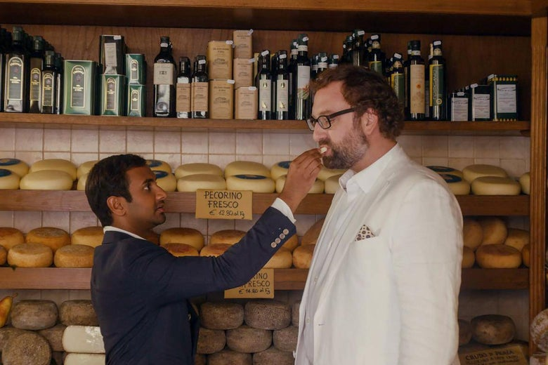 Dev feeds Arnold some cheese in an Italian cheese shop.