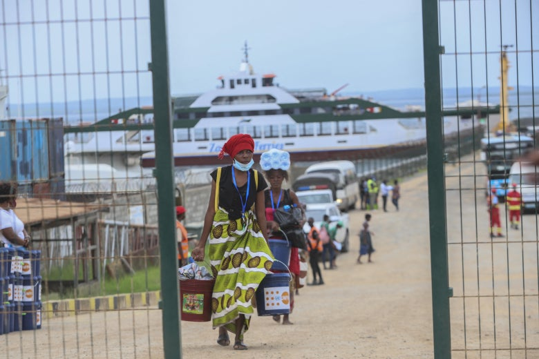 With a large ship on the water in the background, people carrying possessions walk up a dirt path toward an open gate in a fence.