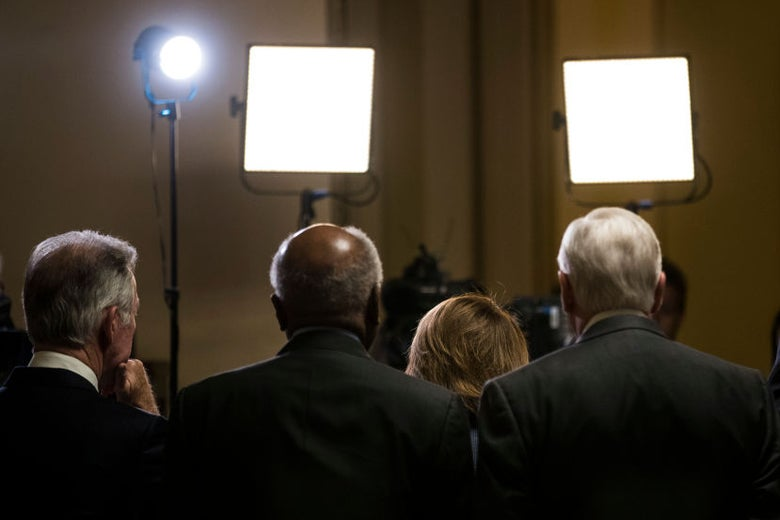 The four Democrats are seen from behind in the glare of TV lights.