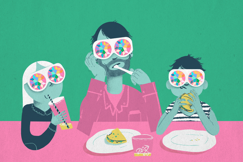 A man and two children wearing kaleidoscope glasses eat at a table.