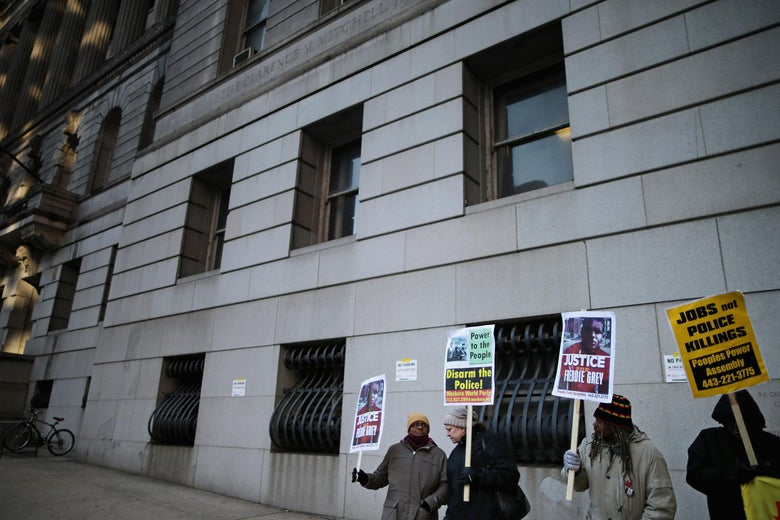 A group of protesters outside a courthouse hold signs demanding justice for Freddie Gray