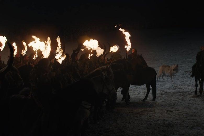 Melisandre sets a group of Dothraki swords on fire.