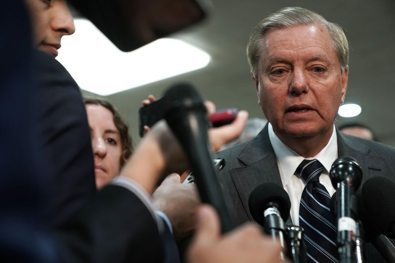 Graham surrounded by microphones and reporters.