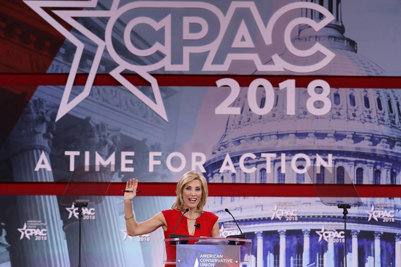 Laura Ingraham raises her right hand while addressing the crowd at CPAC 2018.