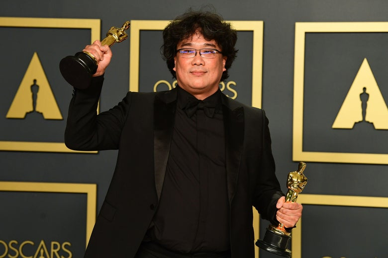 South Korean director Bong Joon-ho poses in the press room with his trophies.
