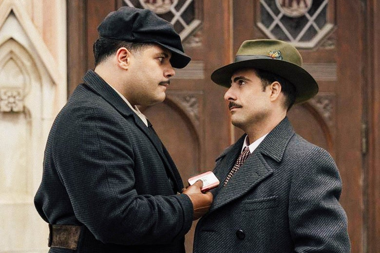 Two men with mustaches and hats stare at each other, one carrying a small tin, in a still from Fargo.