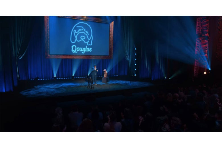 A still from Douglas showing Hannah Gadsby onstage in front of a screen displaying a neon blue line sketch of her dog.