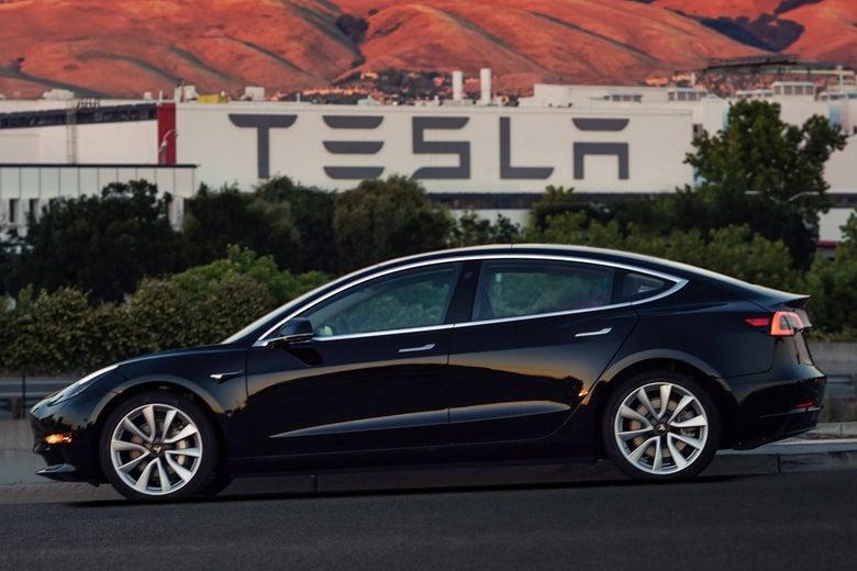 The Tesla Model 3 drives past a Tesla factory.