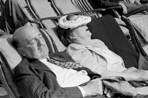 An American couple sleeping in the Atlantic sunlight on board the Cunard liner Queen Elizabeth as she makes her way to Britain.