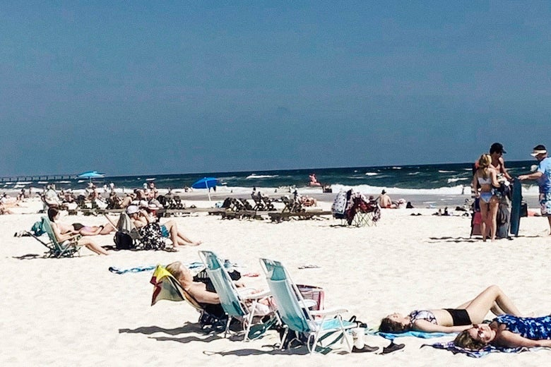 People lounging on beach chairs and towels on a sunny day at the beach