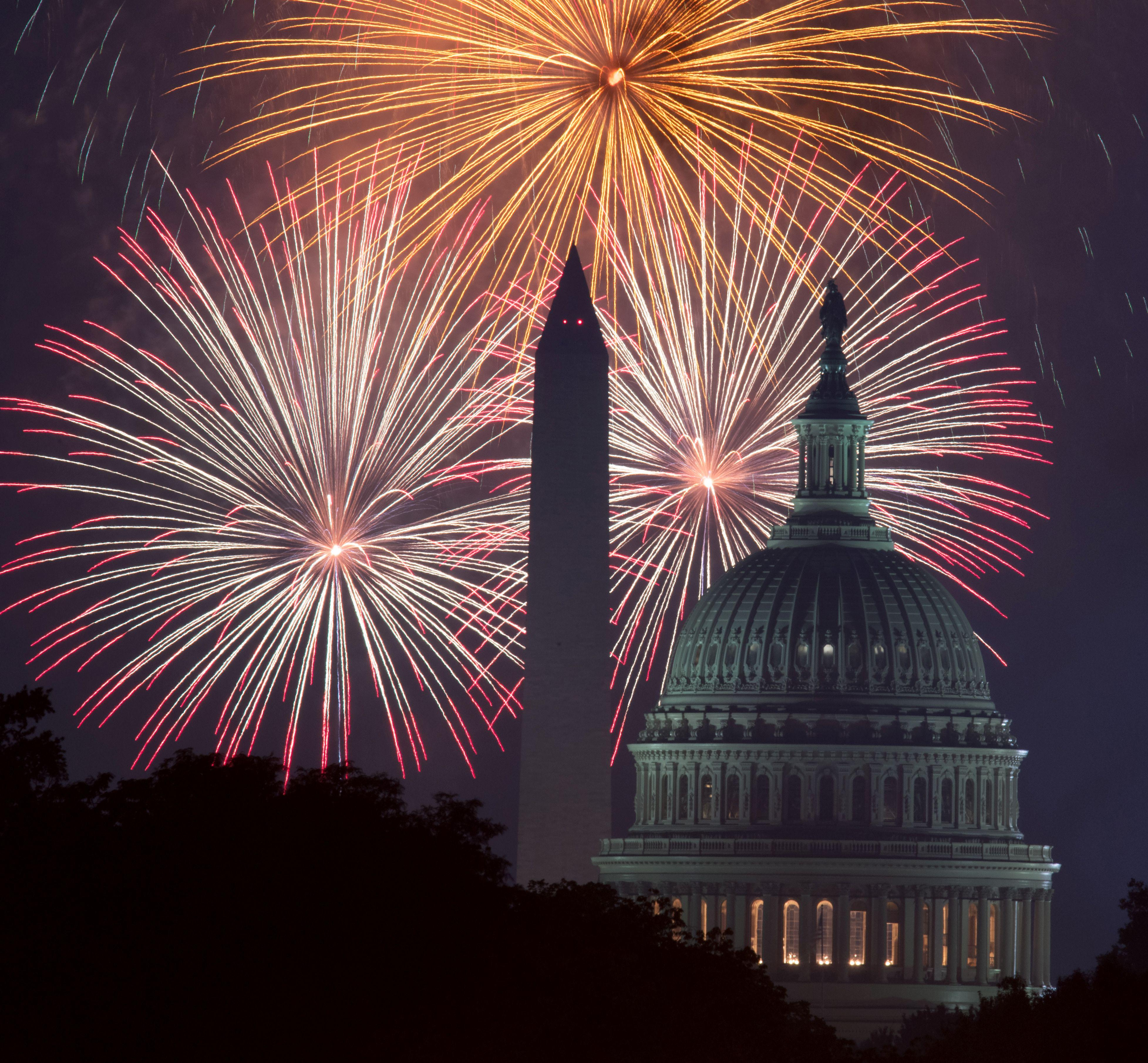 Fireworks explode over the National Mall in Washington, DC, as the US Capitol (R) and National Monument (C) are seen in the foreground.