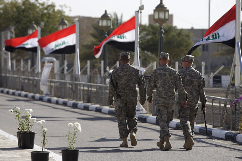 Iraqi flags fly in the wind as US soldiers leave Al-Fao palace at Camp Victory, one of the last US bases Iraq, after a special ceremony in Baghdad on December 1, 2011. The United States handed over to Iraqi control the sprawling Victory Base Complex near Baghdad, the main base from which the US war in Iraq was run, a US military spokesman said on December 2, 2011.         AFP PHOTO/POOL/KHALID MOHAMMED (Photo credit should read KHALID MOHAMMED/AFP/Getty Images)